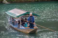 Arashiyama travel. Kyoto, Japan - November 26,2015 :  Unidentified people sail boates in the Oi river for tourist who travel to Arashiyama mountain area in Kyoto Royalty Free Stock Photography