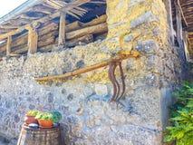 aratro antico appeso sulla parete di pietra della casa di campagna fotografie stock