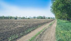 Aratura del trattore su un campo di azienda agricola della molla Fotografia Stock