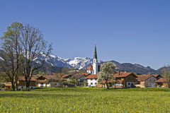 Arbach in spring. The idyllic village church of Arzbach with snowy Benediktenwand in spring Stock Photo