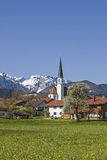 Arbach in spring. The idyllic village church of Arzbach with snowy Benediktenwand in spring Royalty Free Stock Images