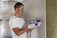 Arbeider in beschermende brillen die met schroevedraaier aan isolatie werken Drywal royalty-vrije stock afbeeldingen