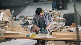 Arbeider in beschermende hoofdtelefoons die met hout werken die riemschuurmachine het oppoetsen gebruiken stock footage