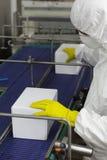 Arbeider bij automatische lopende band in fabriek stock afbeelding
