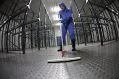 Arbeider in blauwe, beschermende overtrekken die vloer in leeg pakhuis schoonmaken stock fotografie