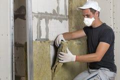 Arbeider in de beschermende isolatie van de de rotswol van het ademhalingsapparaatmasker isolerende in houten kader voor toekomst stock afbeeldingen