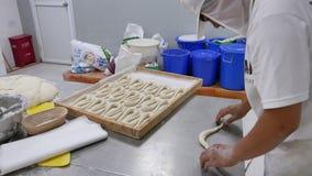 Arbeider in de industriële pretzels van het bakkerij rollende deeg stock footage