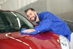 Arbeider die automobiele bonnet schoonmaken bij autowasserette royalty-vrije stock afbeelding