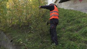 Arbeider die bijl met behulp van bij in openlucht dichtbij struiken stock videobeelden
