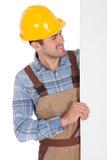 Arbeider die bouwvakker draagt en lege banner houdt Stock Foto