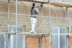 Arbeider die buitenmuur van onlangs gebouwd huis pleisteren royalty-vrije stock foto's