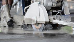 Arbeider die cirkelzaag gebruiken om beton te snijden stock footage
