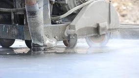 Arbeider die cirkelzaag gebruiken om beton te snijden stock video