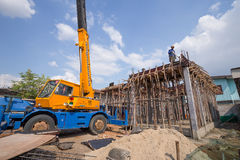 Arbeider die concrete plak met mobiele kraan gieten om een huis te bouwen Stock Afbeeldingen