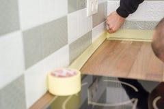 Arbeider die countertop in keuken met afplakband beschermen alvorens bouwreparaties met keramische tegels te beginnen stock foto