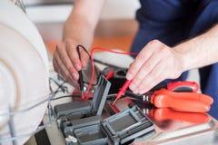 Arbeider die de afwasmachine in de keuken herstellen stock foto