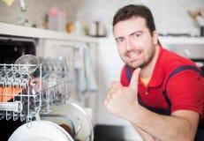 Arbeider die de afwasmachine in de keuken belangrijkste nadruk herstellen op de hand stock foto