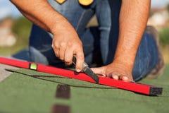 Arbeider die de dakspanen van het bitumendak installeren Stock Foto