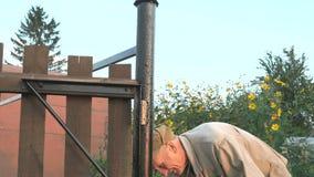 Arbeider die de ijzeromheining schilderen die zwarte verf gebruiken stock videobeelden