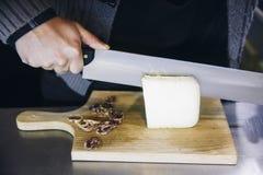 Arbeider die de kaas snijden stock afbeelding