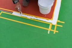Arbeider die de nevenactiviteit op de vloer schilderen Royalty-vrije Stock Afbeeldingen