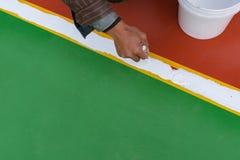 Arbeider die de nevenactiviteit op de vloer schilderen Stock Foto