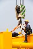 Arbeider die de opheffende riem plaatsen Stock Afbeeldingen