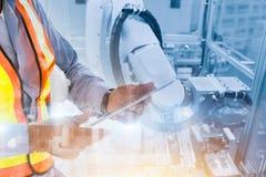 Arbeider die de robotwapen van de tabletcontrole in productielijn met behulp van stock foto's
