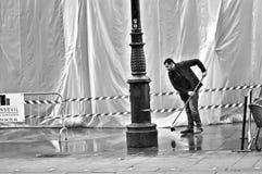 Arbeider die de vloer vegen Stock Foto's