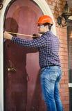 Arbeider die deur met het meten van band meten Royalty-vrije Stock Afbeeldingen