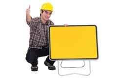 Arbeider die door verkeersteken knielen Stock Foto's