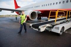 Arbeider die door Transportbandvrachtwagen lopen met Vliegtuig op Baan stock foto's