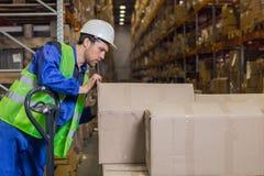 Arbeider die dozen met koopwaar in pakhuis controleren royalty-vrije stock foto
