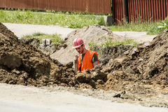 Arbeider die een geul voor riool graven Stock Fotografie