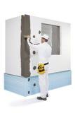 Arbeider die een hoek-lat met een laag bedekken met een stopverf Stock Foto's