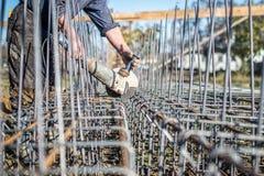 Arbeider die een hoekmolen met behulp van die staalbars te snijden voor versterking worden gebruikt Stock Foto's