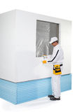Arbeider die een klein isolatiepaneel bevestigen Stock Fotografie