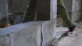 Arbeider die een muur van geluchte concrete blokken bouwen stock videobeelden