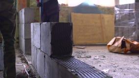 Arbeider die een muur van geluchte concrete blokken bouwen stock footage