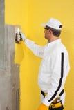 Arbeider die een pleister op een hoek-muur uitspreiden Royalty-vrije Stock Foto