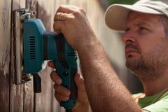 Arbeider die een trillende schuurmachine op een houten omheining met behulp van stock afbeeldingen