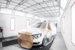 arbeider die een witte auto in speciale garage schilderen, die kostuum en beschermend toestel dragen stock foto's