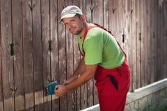 Arbeider die elektrische schuurmachine met behulp van om oude verf te verwijderen stock afbeelding