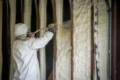Arbeider die gesloten het schuimisolatie van de celnevel op een huismuur bespuiten stock foto's