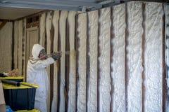 Arbeider die gesloten het schuimisolatie van de celnevel op een huismuur bespuiten stock foto