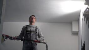 Arbeider die hand oppoetsende machine met behulp van om gipsplaatplafond op te poetsen stock footage