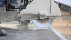 Arbeider die het beton met een zaag snijden stock video