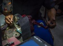 Arbeider die het facetteren van halfedelsteen op malende machine in de juwelenworkshop maken stock foto's
