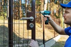 Arbeider die het slot voor de nieuwe poorten van de metaalomheining installeren stock afbeelding