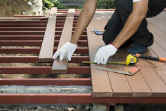 Arbeider die houten vloer voor terras installeren Stock Foto